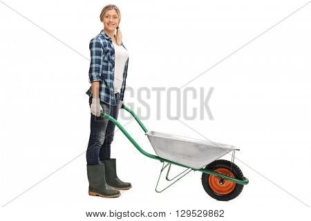 Cheerful woman posing with an empty wheelbarrow isolated on white background