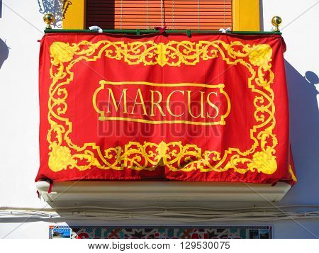 Alora Spain March 25 2016: Balcony decorated with name of Apostle as part of Easter processions. Alora Spain March 25 2016