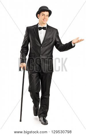 Full length portrait of a young gentleman in a fancy black suit walking with cane isolated on white background