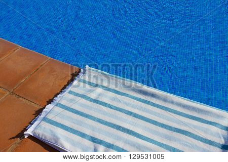 resort background with striped towel  near pool  clear blue  water