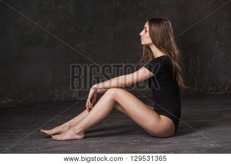 Attractive girl in black bodysuit at the dark studio sitting on the floor and looking to the left
