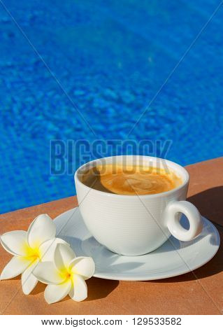 white cup of coffee near pool blue water with copy space