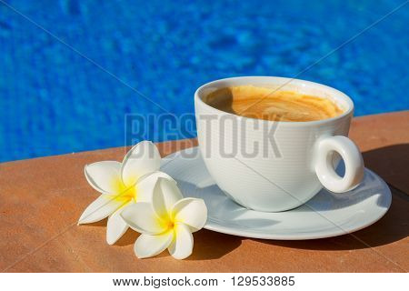 white cup of coffee with fresh flowers on the edge of pool