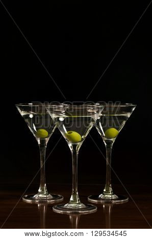hree glasses of martini cocktail on a black background