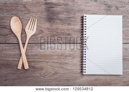 Wooden Spoon, Fork And Lined Paper On Wooden Table Top View
