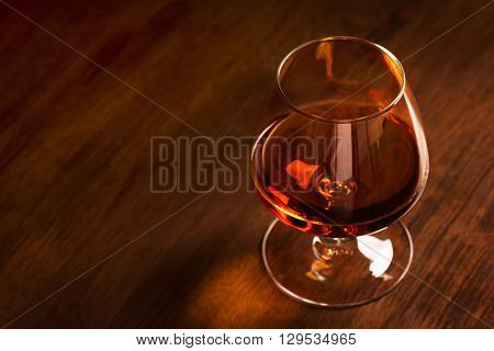 A glass of French cognac on a wooden table (with copy space)