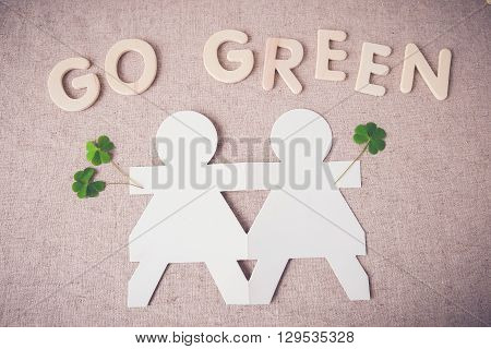 paper dolls holding hands with green leaves and 'GO GREEN' word