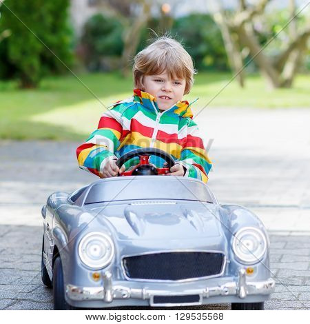 Child of 3 years driving big toy old vintage car and having fun, outdoors. Active leisure with kids outdoors  on warm spring or autumn day.