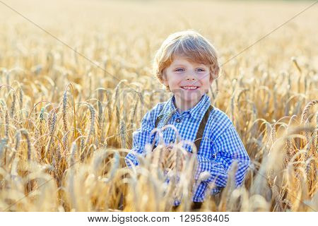 Funny little kid boy in traditional German bavarian clothes, leather shorts and check shirt, walking happily through wheat field near  hay stack or bale. Active outdoors leisure with children on warm summer day.