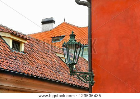 Traditional street lamp and the tiled roofs of Prague Czech Republic
