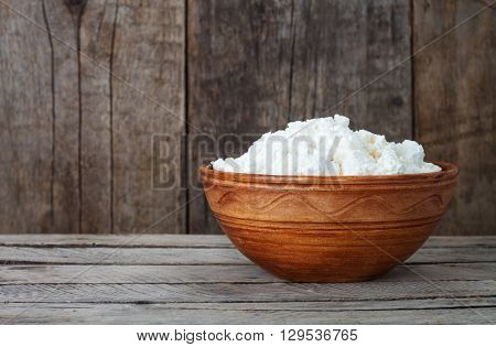 Cottage cheese on a wooden background. Fresh cottage cheese in ceramic dish on wooden boards. Dairy product