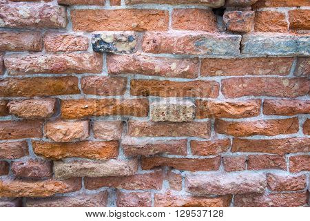 the old textured surface of a red brick wall for wallpaper and for a background