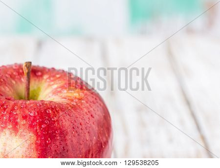 Close up fresh red apple on wooden table background