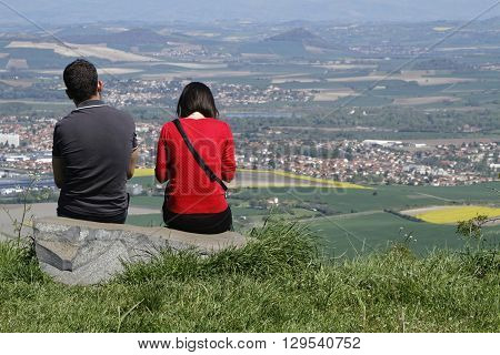 GERGOVIE FRANCE May 5 2016 : Young couple on the Gergovie Plateau look at landscape of the Plaine des Sarlieves.
