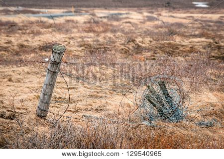 Fence With Barb Wire On A Field