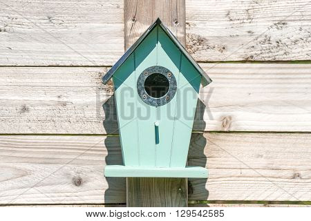 Blue Birdhouse On A Wooden Fence