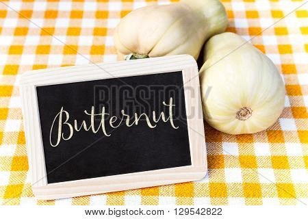 Butternut squash on a chequers tablecloth and a slate with Word Butternut