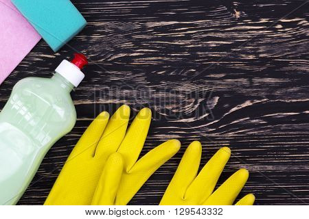 Detergent, sponge, rag and latex gloves on wooden background