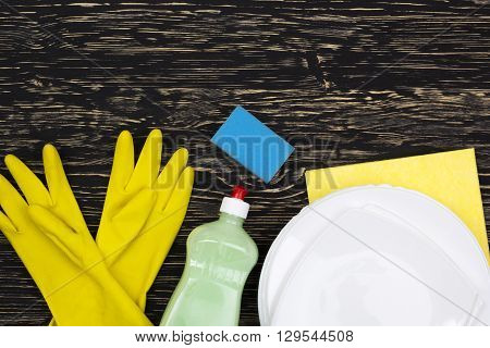 Detergent, sponge, dishes, rag and latex gloves on wooden background