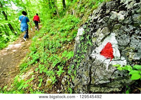 Hiking red triangle paint marking on a rock with hiker on the trail