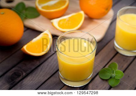 Freshly squeezed orange juice in glass with fruits on wooden background