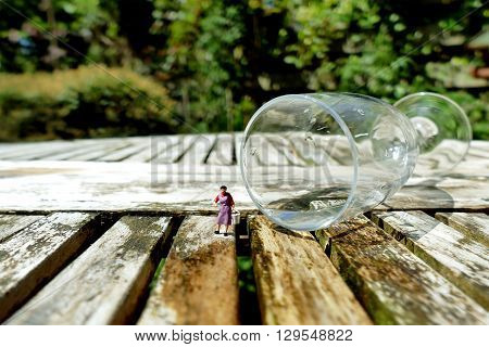 Miniature Woman Collecting Water With Bucket From Fallen Champagne Glass