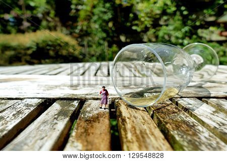 Miniature Woman Collecting Champagne With Bucket From Fallen Champagne Glass