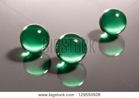 three green balls reflecting on mirror surface