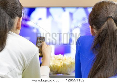 Two teenager girls with remote control laying down and watching smart tv eating popcorn.