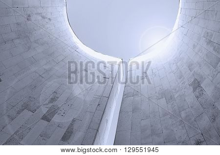 Perspective bottom view of semicircular walls built in urban futuristic style. Architecture urban background with reflected lights. Modern architecture cityscape in cold futuristic tones.