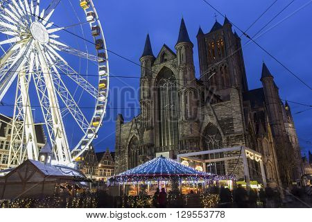 Saint Nicholas' Church in Ghent in Belgium with a ferris wheel in the foreground