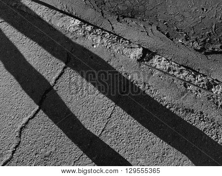 Diagonal shadows on the fractured asphalt sidewalk and border