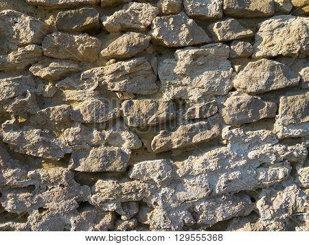 Sunlit beige wall of the rough sandstones