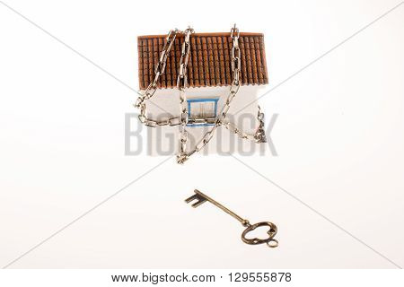 key and a house in chains on a white background