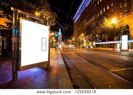 blank billboard on road with tramway in san francisco at night