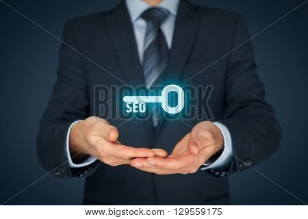 Key to successful SEO - search engine optimization concept. Businessman is looking for key to improve website traffic.