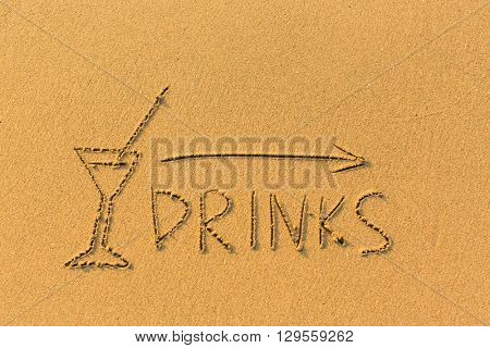 Pointer arrow, glass and the words Drinks drawn on the sand beach.