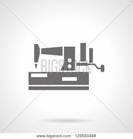 Sewing machine with handle. Household sewing equipment with manual control. Homemade craft. Symbolic black glyph style vector icon. Element for web design and mobile.