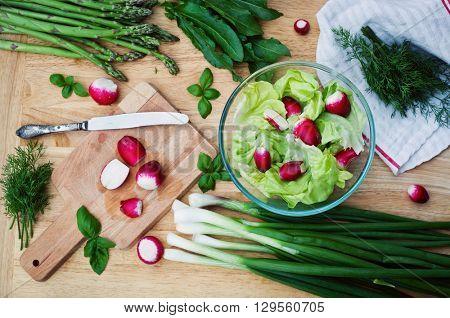 Green spring vegetables on wooden table - radish, lettuce, asparagus, onions, dill, sorrel