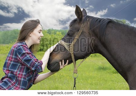 Friendship between teenager girl and cute mare