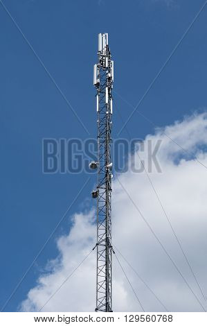 Cell phone tower, blue sky with clouds