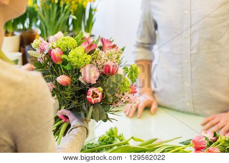 people, shopping, sale, floristry and consumerism concept - close up of florist woman making bouquet for and man or customer at flower shop
