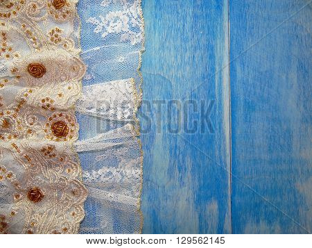 white lace embroidered with beads and Golden thread lies on blue wooden boards