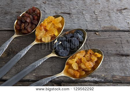 Raisins In Metal Spoons On Wooden Table