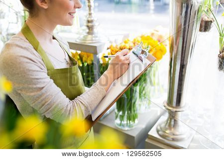 people, sale, retail, business and floristry concept - close up of happy smiling florist woman with clipboard writing and making notes order at flower shop