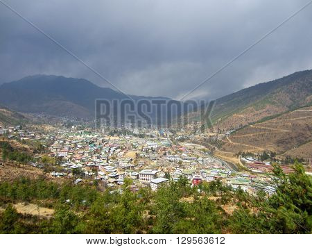 Bhutan city in a valley with hills surrounding it and rain clouds rolling over