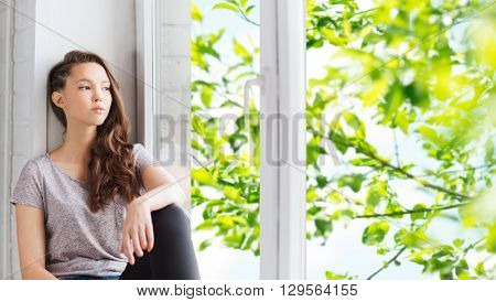 people, emotion and teens concept - sad unhappy pretty teenage girl sitting on windowsill and looking through window over green natural background