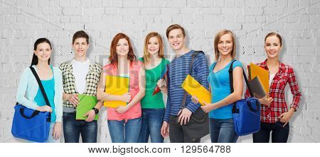 education, school and people concept - group of smiling teenage students with folders and school bags over gray brick wall background