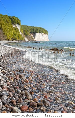 Beach With Stones And Chalk Cliffs In Distance.