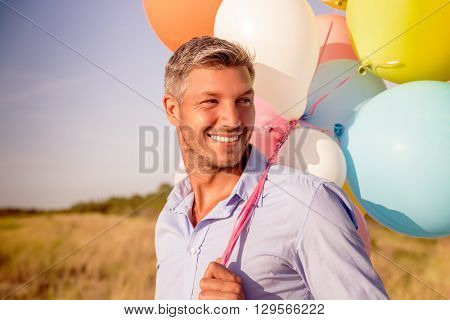 happy man walking with balloons